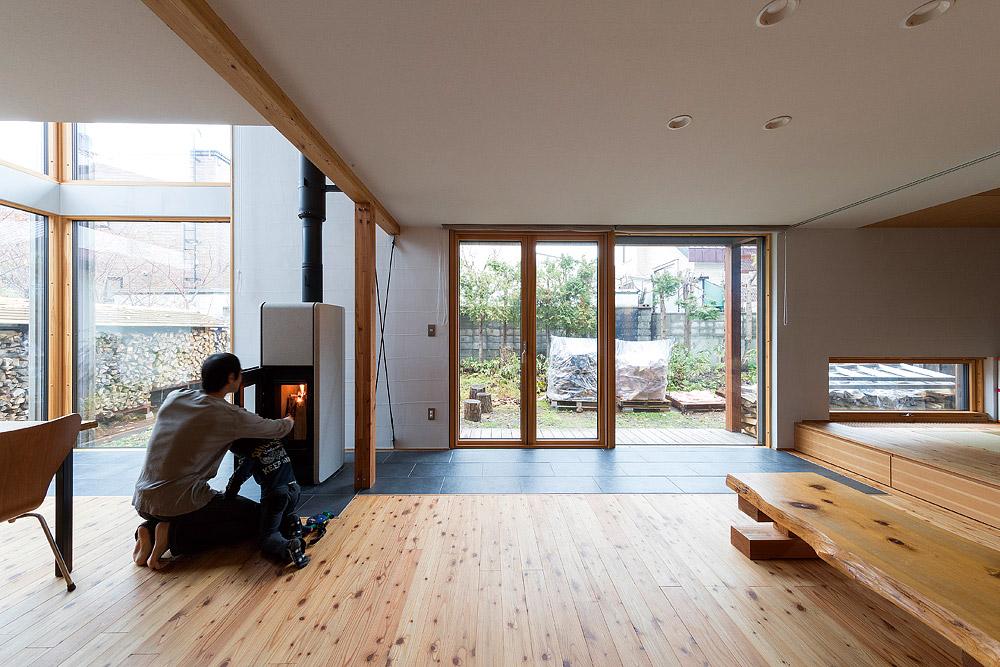 庭に面した南向きの窓前は土間仕上げで冬は日射を蓄熱。ナチュラルなデザインの室内に薪ストーブが調和する