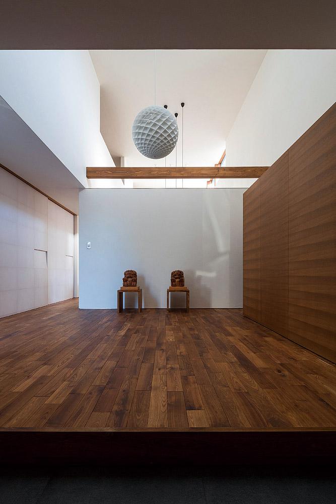 吹き抜けの開放感とエンジュの無垢床の質感が際立つ玄関ホール。木彫りのシーサーは、Sさん宅の守り神