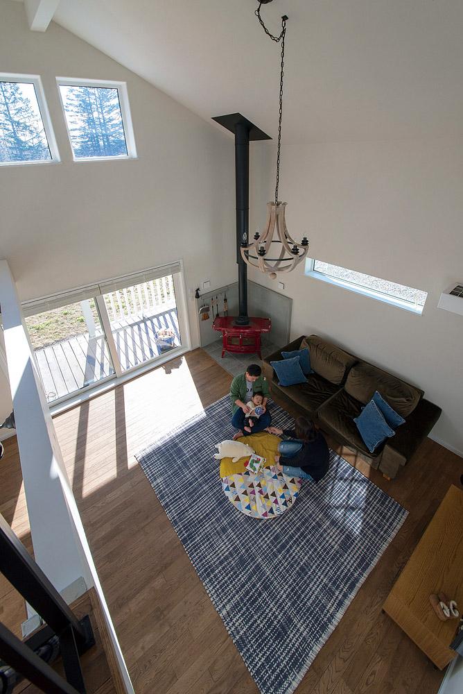 2階ホールからリビングを見下ろす。レッドの薪ストーブがナラ無垢フローリングの落ち着いた空間のアクセントに