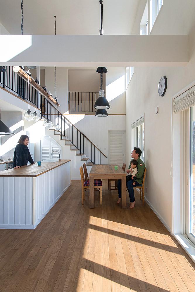 加熱部とシンク部分を背中合わせにしたオープンなキッチン。天井にぶら下げた焼きスギの丸太につけた照明が個性的だ。左側の扉はパントリー。見た目より奥行きがあり収納力抜群