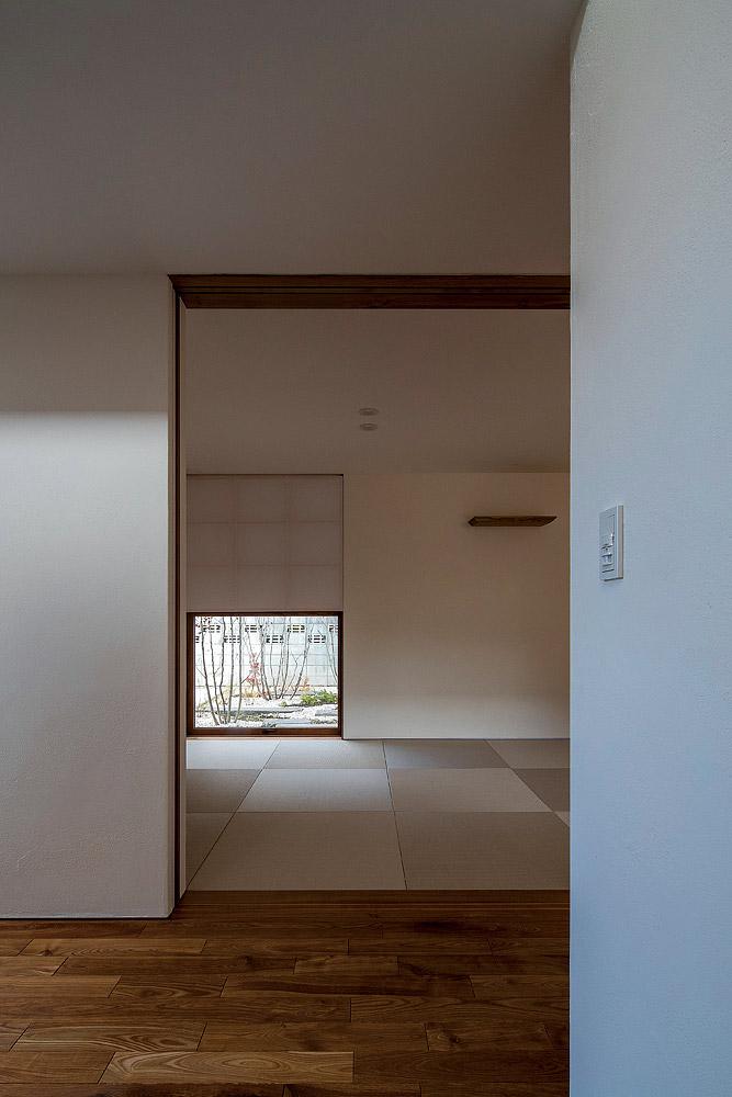 客間として機能する和室は玄関横にレイアウト。地窓からは、緑と札幌軟石を配した小さな庭が見える