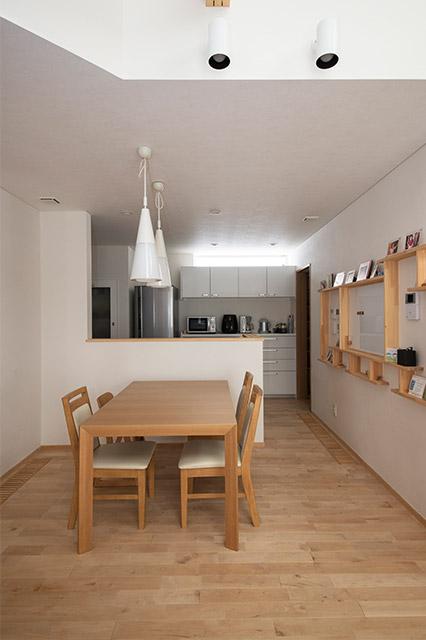 ダイニングから見た対面キッチン。右側の壁面飾り棚は奥さんのイラストが参考になったもの