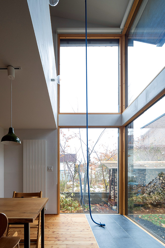 吹き抜けのリビングには外付けのブラインドを 設置したL字型の大きな窓があり開放感が格別。 吹き抜けには子どもが遊べる上り綱もある