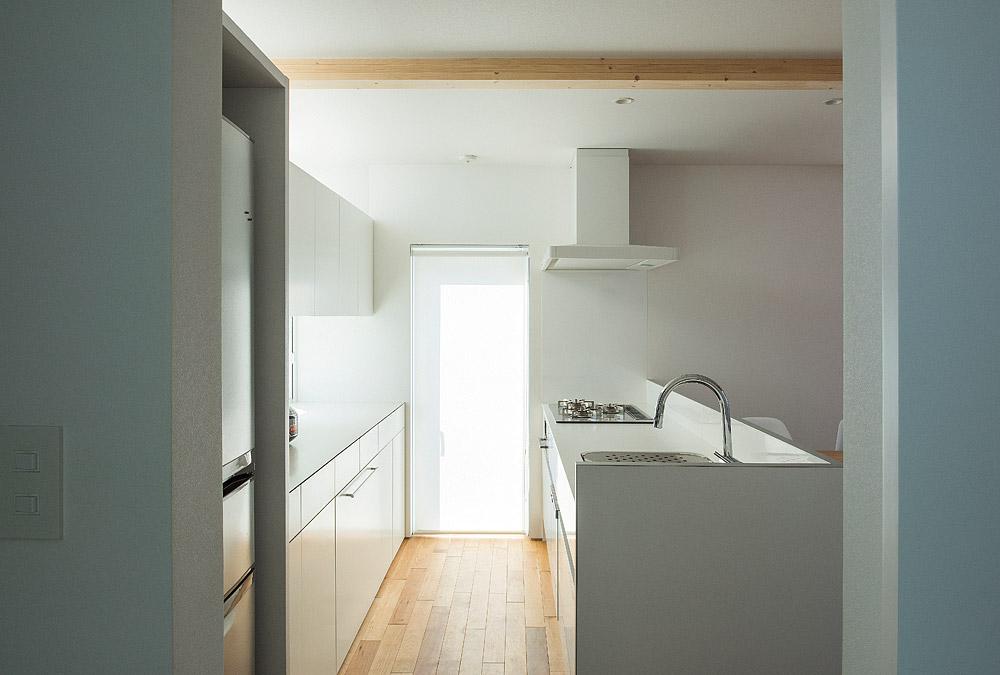 ユーティリティからキッチン内部を見る。自然光を確保した明るく作業性の高い空間