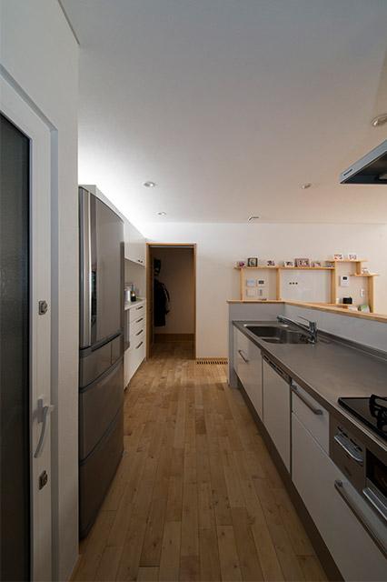 キッチンからシューズクロークまでの回遊動線。手前左側にパントリーなどが設置され機能的なキッチン