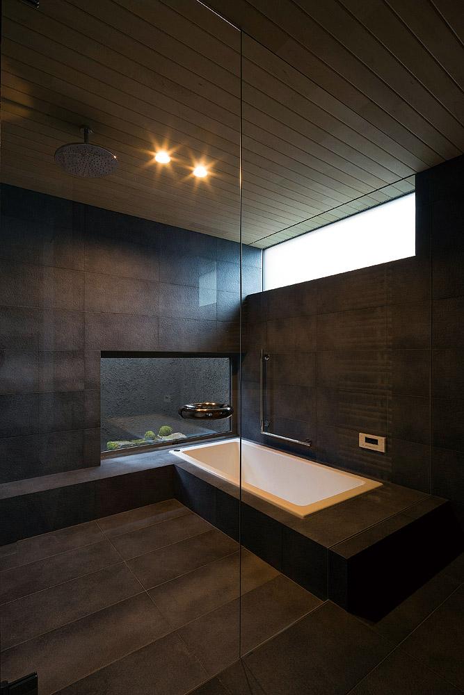 ヒバの香りが清々しいタイル張りの造作浴室。坪庭を望む開口が設けられ、湯に浸かり緑が楽しめる
