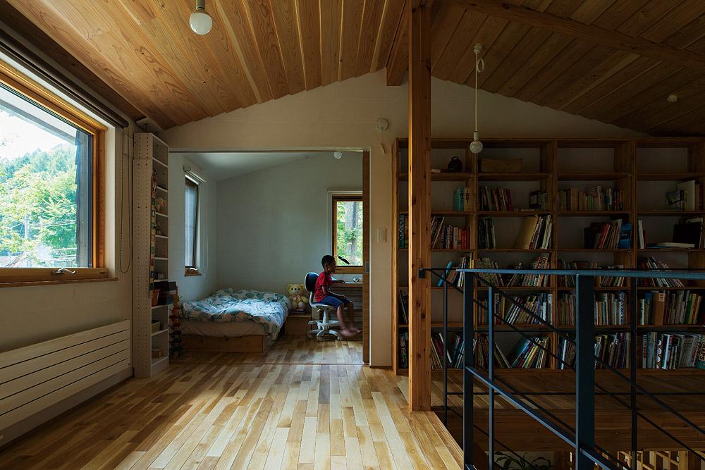 階段ホールの南西側に設けられた子ども室。ホールの壁には、家族共用の本を収める造作本棚が設けられている