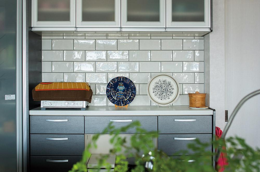 キッチンのカウンター収納と吊り棚の間の壁は、奥さんが大切にしてきた飾り皿がより映えるようタイル張りに変更