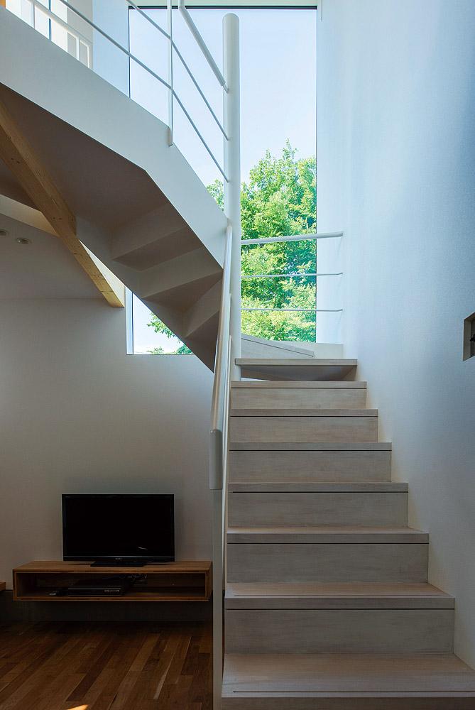 リビングから2階へ繋がる階段。吹き抜けと近隣の緑を取り込む大開口部が、開放的な空間を生む