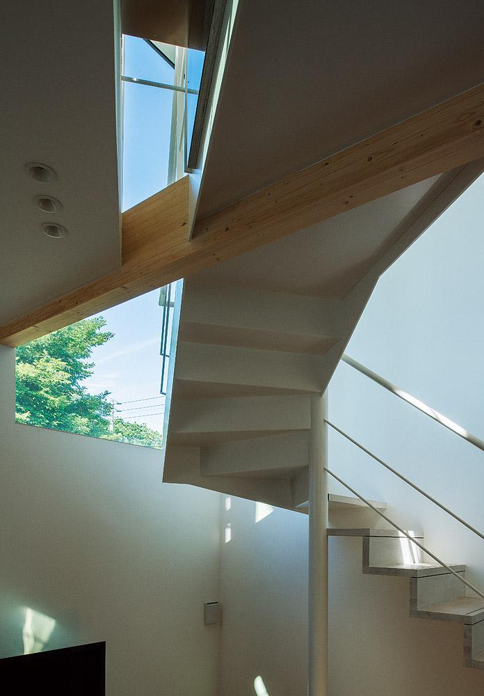 リビングから吹き抜けを仰ぎ見る。階段の造形美と窓越しの景色が交錯する建築的な見せ場