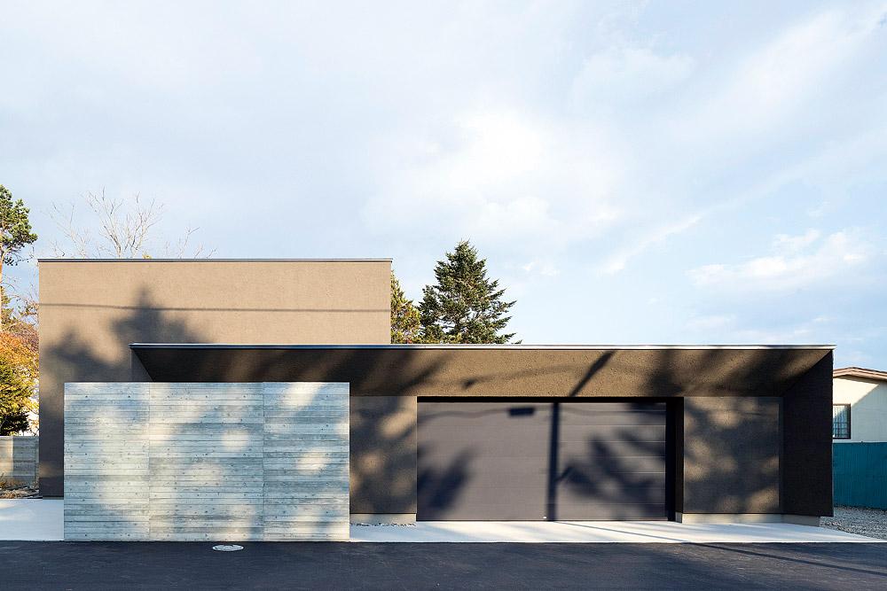 木立の影を浮かべ、閑静な住宅街に溶け込むように佇むファサード。右手は、外物置を兼ねた車庫