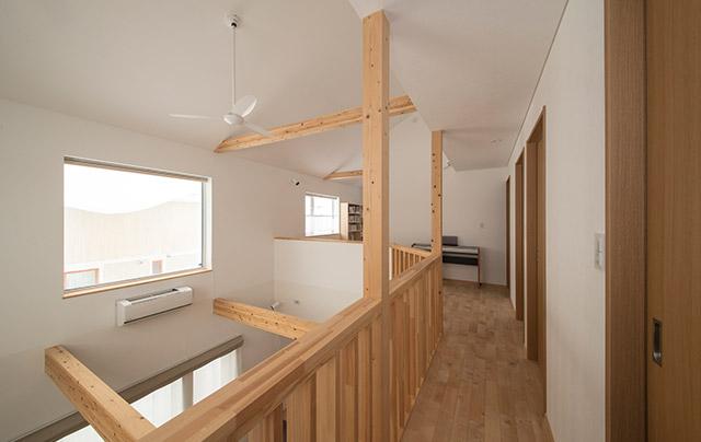 廊下の突き当たりから見た吹き抜け上部と高窓。美しく露出した梁もアクセントに