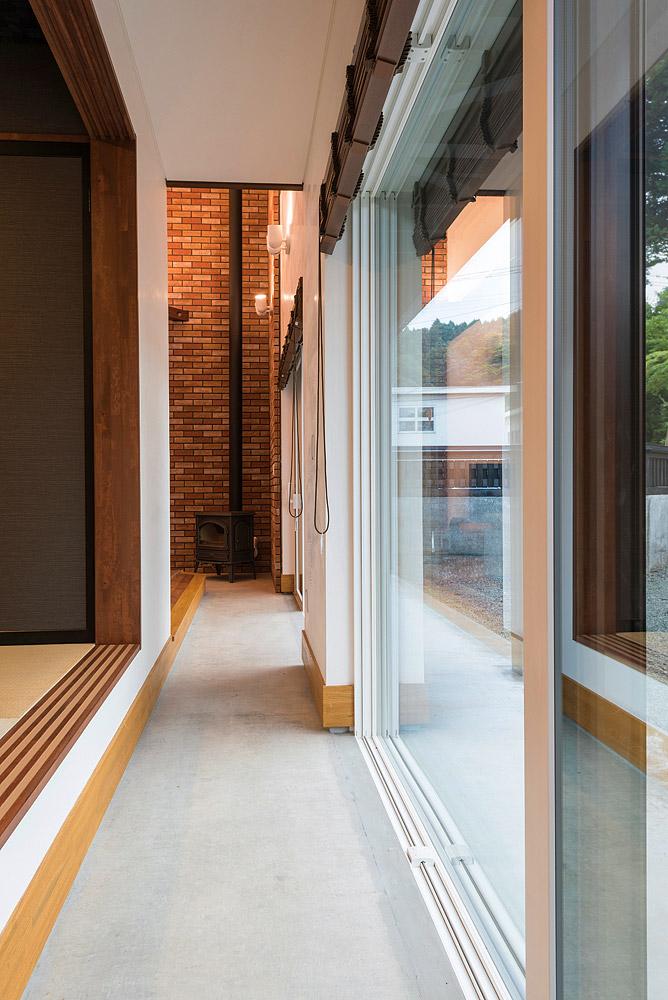 玄関からリビング奥の薪ストーブへ続くコンクリート土間。昔の日本家屋のように外との繋がりを感じる空間だ