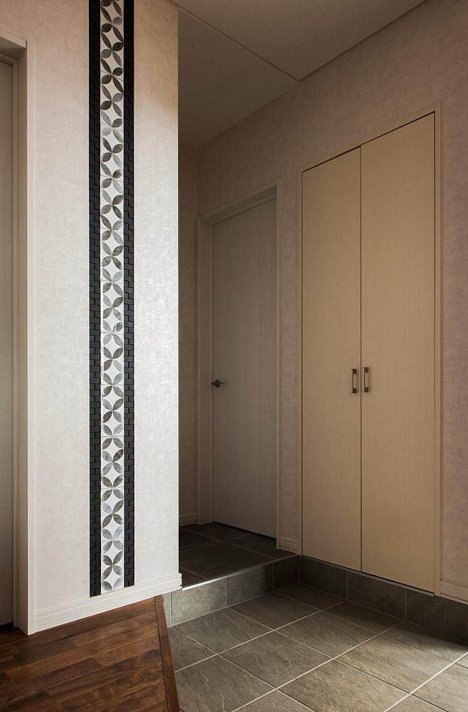 玄関脇にあった既存の洋室は2分割し、玄関側を靴のまま出入りできる納戸に、ホール側をピアノと趣味の部屋につくり変えた。ホールの壁には、奥さんが好きそうなデザインのタイルを選んで、絵のように張り、他にはない特別な空間をつくり上げた
