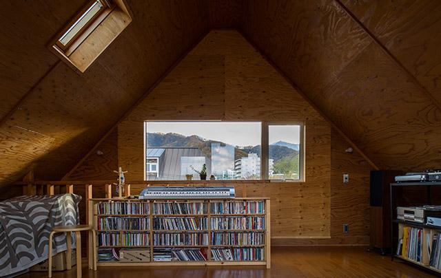 屋根裏のような雰囲気の3階はご主人の趣味部屋。レコードやCDがずらりと並ぶ。窓を小さくすることで結露もなくなり、断熱性能アップで暖かな空間に
