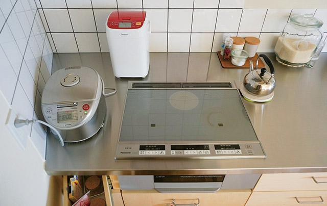 キッチンのステンレス天板は一品ものなので斜めの壁にぴったり。奥の引き出しも斜めにしつらえて、出し方にもひと工夫
