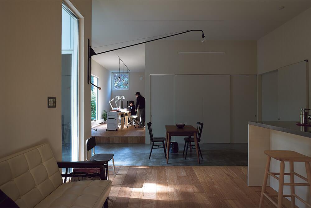 リビングから仕事の場である多目的スペースを見る。床レベルを他のスペースより下げた土間が、仕事とプライベートを分ける境界になっている