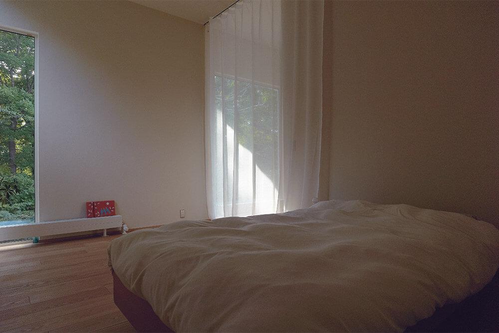 寝室とLDKの間仕切りは柔らかく光を透すレースのカーテンで