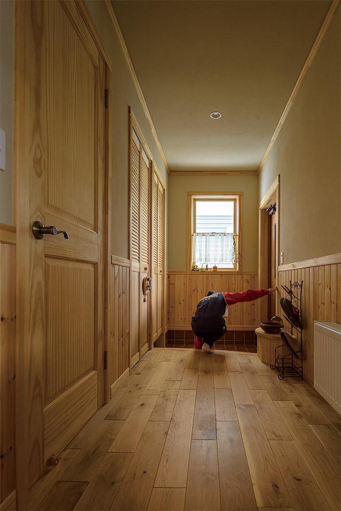 パインの造作建具、ナラ無垢床が心地よい玄関。土間左手には、靴のまま出入りできるシューズクロークがある