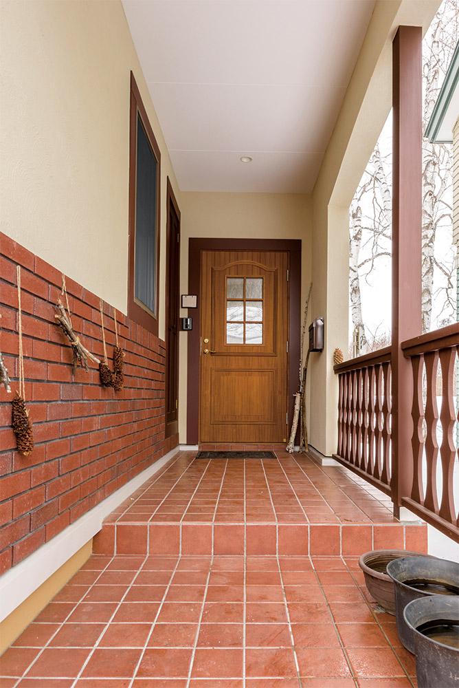 造作木製フェンスとレンガの質感が温かな雰囲気を醸し出す玄関アプローチ。玄関ドアは、スウェーデン製断熱ドア