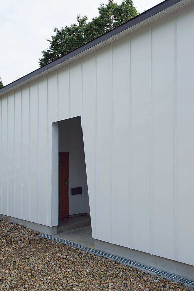 シンプルな矩形の一部を切りとったような小さなポーチ入口。南側の開放的な印象とは対照的なデザイン
