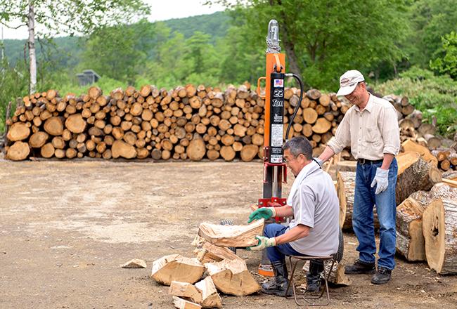 広い土場で効率よく作業を進める「薪割りの会」のメンバー
