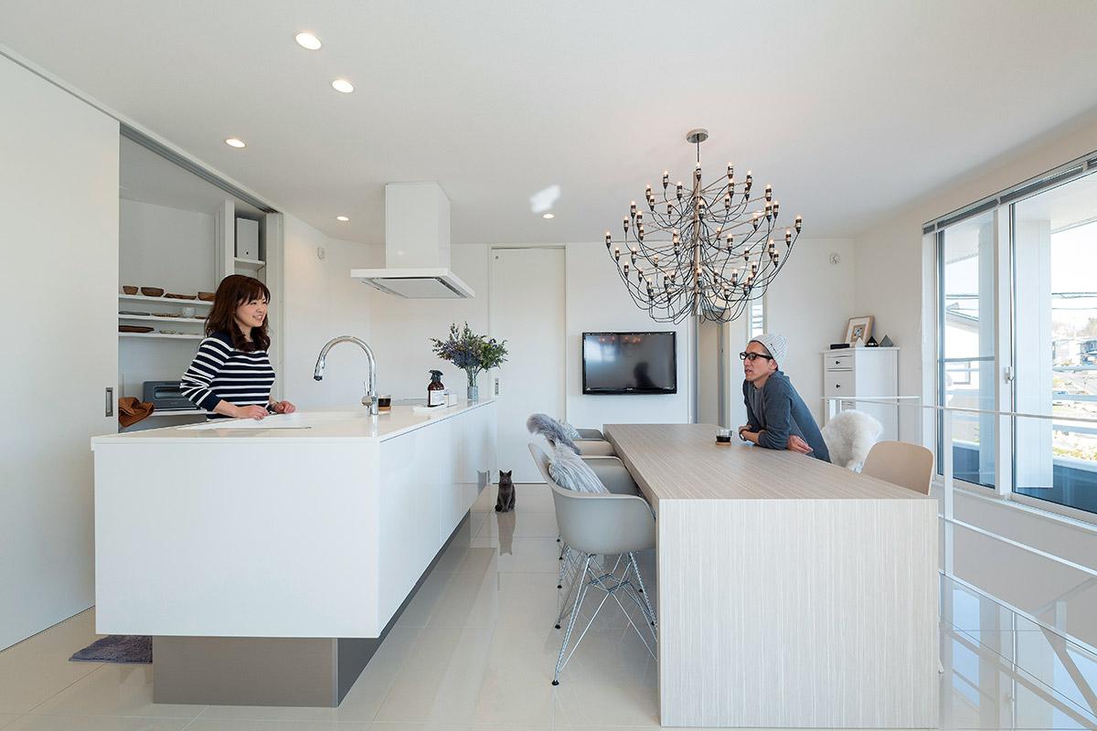福島県郡山市のWさん宅の、料理好きな奥さんこだわりのダイニング・キッチン。白を基調とした開放的な空間に、ボリュームのあるシャンデリアが映える