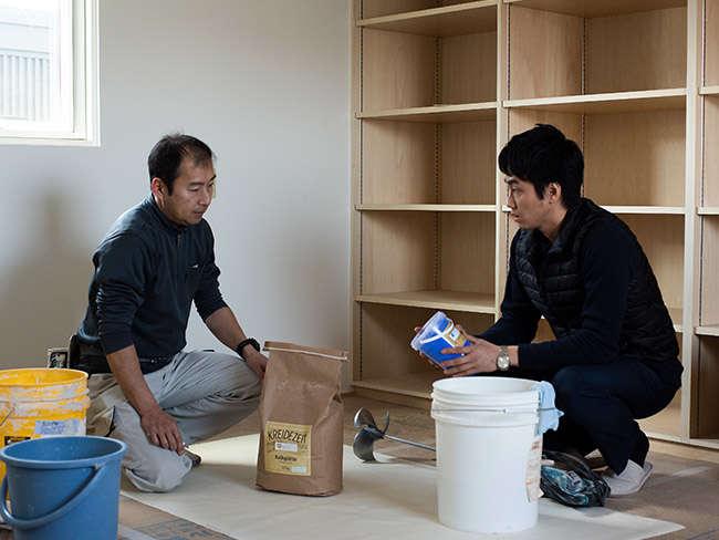 この壁材がどんなものか、左官屋さんに説明するプラネットジャパンの担当者の高山さん(写真右)