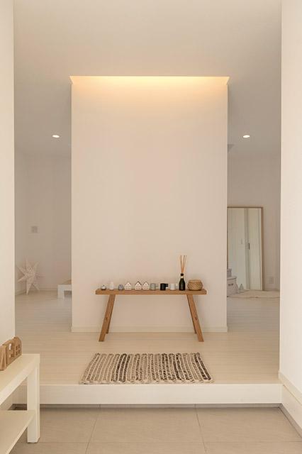 間接照明が照らす白い壁が印象的な玄関。1階は中央にトイレ、その左右にご夫婦の寝室を配したユニークな空間構成となっている