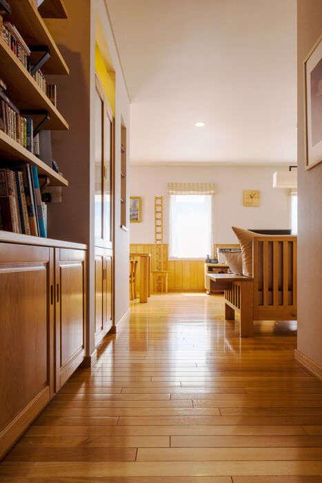 2階ホールからリビングを見る。くつろぎのひと時に気軽に蔵書が手に取れるよう、通路の壁には造作本棚を設置