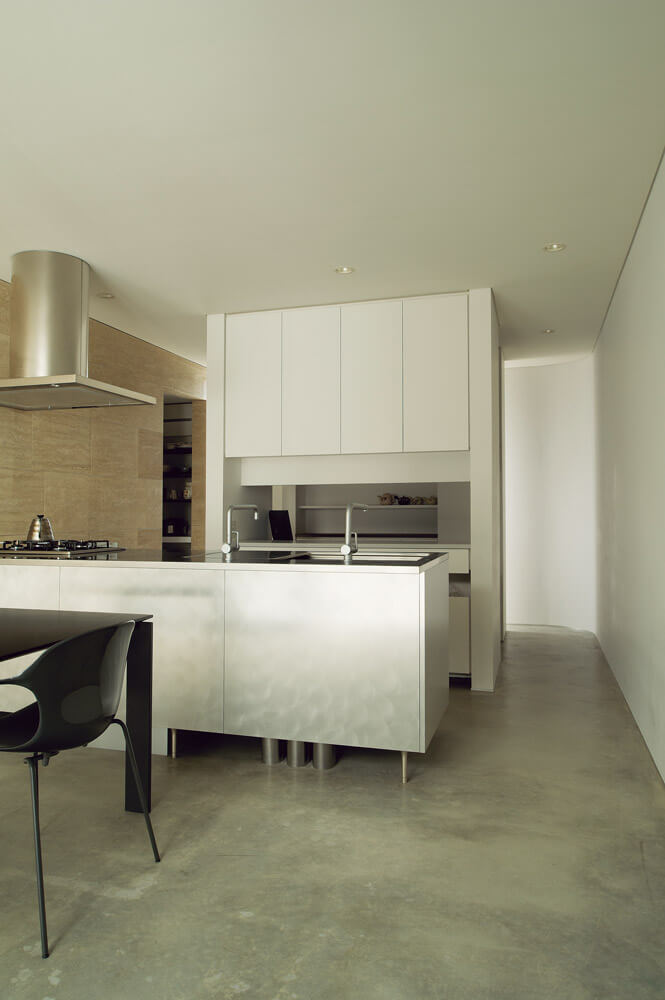 ダイニング・キッチンは、モルタル仕上げの床、大理石タイル張りの壁、ステンレスキッチンの組み合わせ。硬質な空間に、突き当たりからの光がやさしく広がる