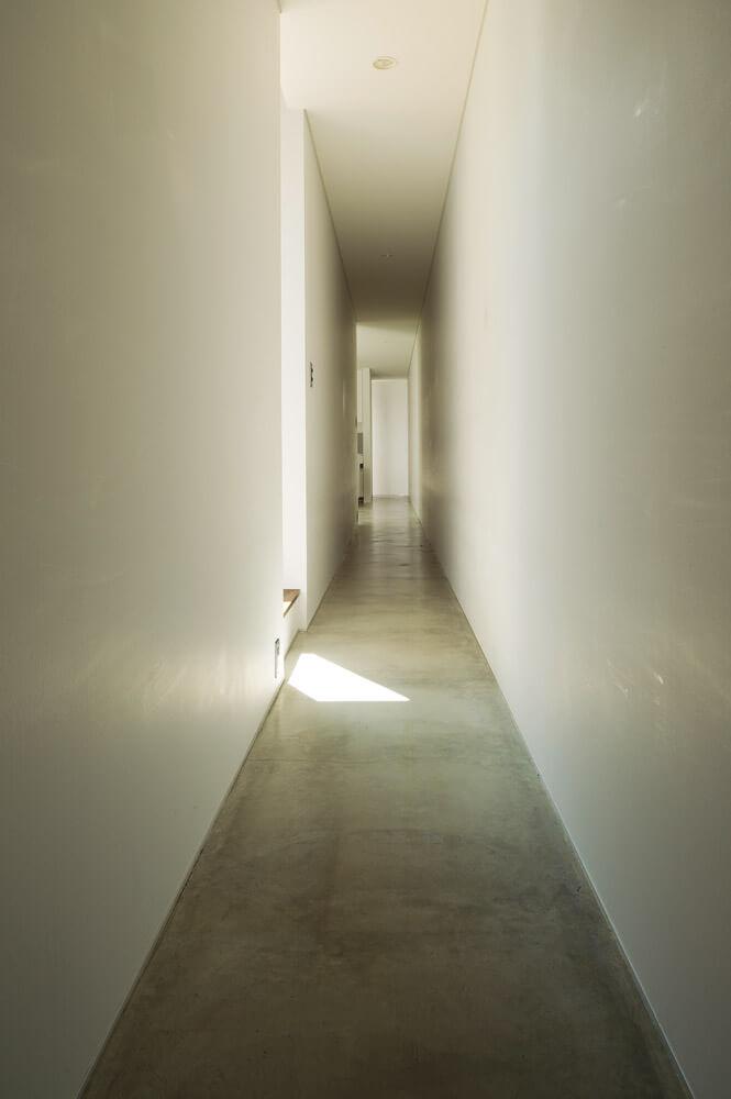 玄関を入り、思わず高揚感に包まれる長い廊下。突き当たりには窓が設けられ、アール状の壁に沿って光が柔らかく拡散する