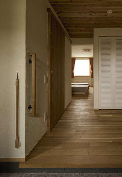 玄関ホールには白塗装で仕上げた収納が設けられている。奥の寝室は10畳の広さ