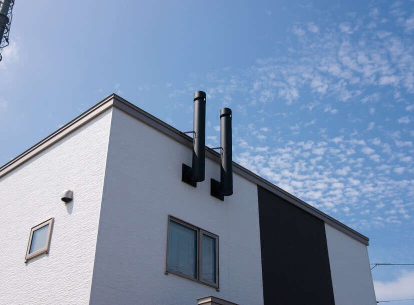 白とこげ茶を組み合わせたシンプルな外観のTさん宅。玄関上の2本の煙突は、湿気と汚れた空気を排出する断熱排気筒