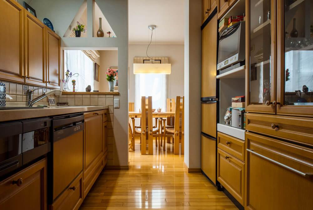 開口部をL字に配した明るいダイニング。キッチンは、一 部をくり抜いた壁で緩やかに分離。キッチンの背面には 造作食器棚をしつらえ、冷蔵庫の扉も木目風のシート を張り、統一感を。端正な納まりも、注文住宅ならでは