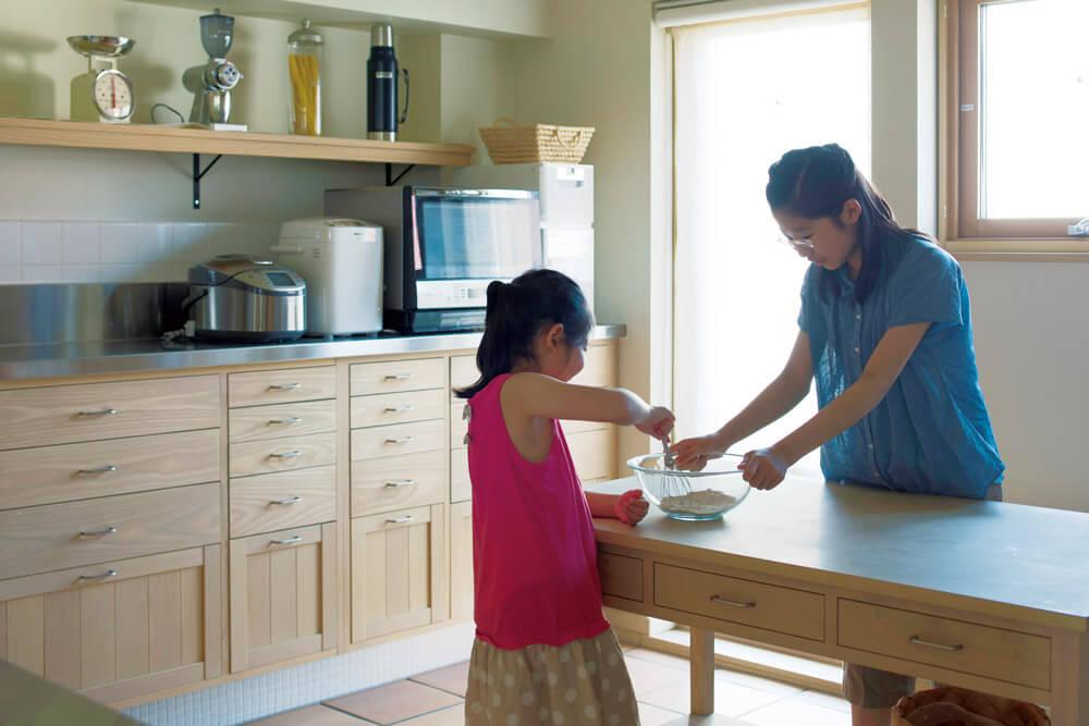 広々としたキッチンは娘さんたちのお気に入り。休日に料理を家族で楽しむのも、築6年を経て日常になった