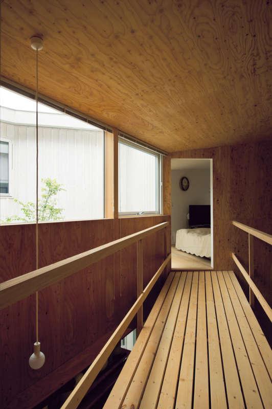 1階のアトリエ上部の吹き抜けは、ブリッジで部屋を行き来する。白い空間から板張りの空間を抜けて、また白い空間へと、周囲の景色だけでなく内装の変化も面白い