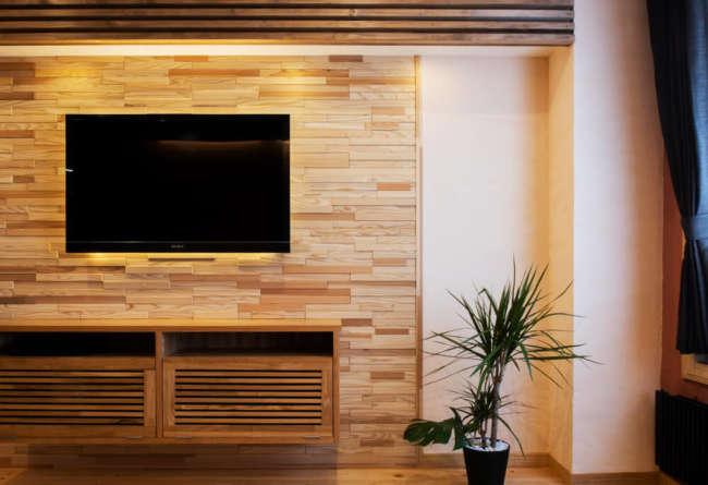 リビングの壁はスギ材をランダムに張り、タモ材の造作収納も設置。随所にしつらえた間接照明がやわらかい雰囲気を演出する