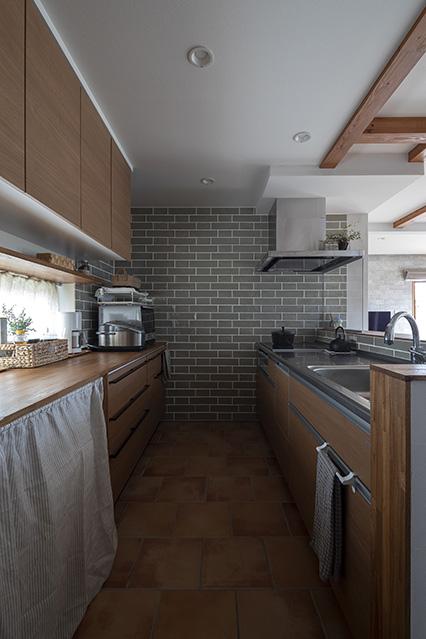 家の中で奥さんが一番気に入っているキッチン。床暖房仕様のタイル床は、少々の汚れならなじんでしまうそう
