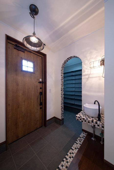 こだわりの玄関スペースはタイルやヴィンテージ感のある照明で演出。手洗いボウルはコーヒーカップ型