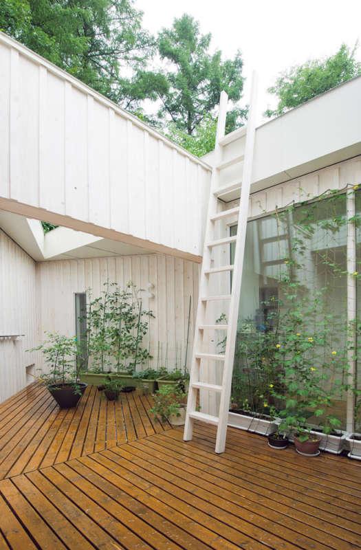 南西にあるゆったりとしたバルコニーは、家庭菜園やハンモックでくつろぐスペースとして利用。アプローチ側には開口を設けず、上部と室内側のみに開いた空間なので、プライベート感が高い。周囲の自然の取り入れ方にメリハリをつけた好例だ