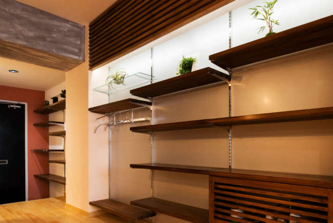 玄関からそのまま続くワンルーム型のLDK。リビング側の壁には、ヒノキ材やガルバリウム鋼板、間接照明を用いて「見せる収納棚」を造作