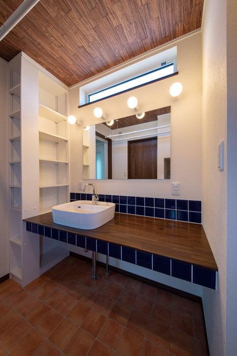 玄関からすぐの造作洗面スペースは照明とタイル、天井の木使いにこだわった。収納棚もたっぷり