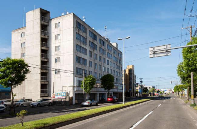 幹線道路に面して建つ築44年のマンション。長く風雪に洗われた外観と、室内のモダンな雰囲気とのコントラストも見どころの一つ