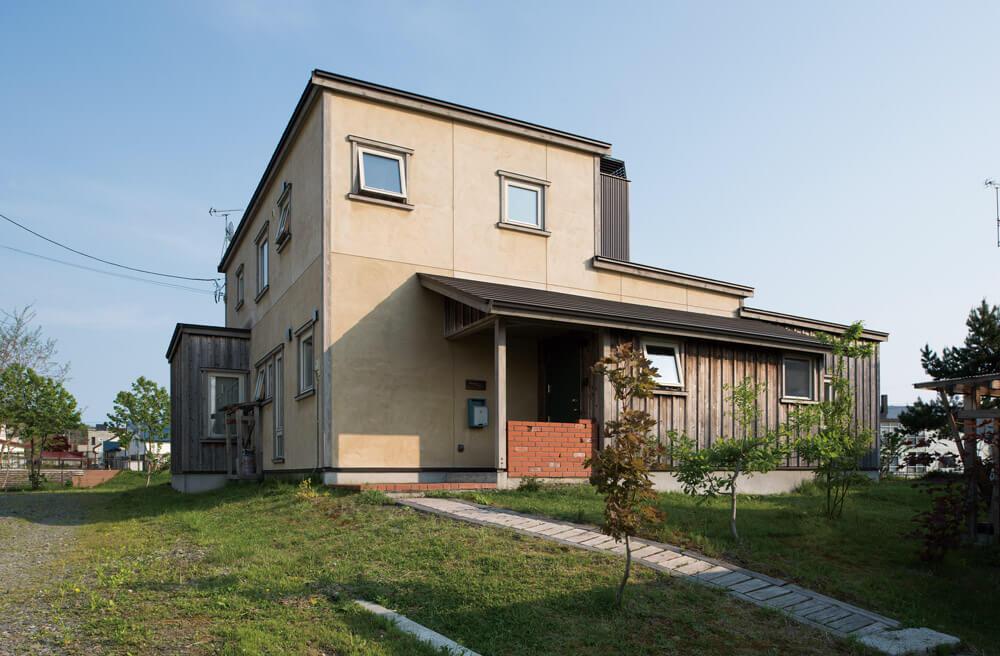 珪藻土とスギ板を組み合わせた外観。前庭やアプローチ、カーポートも、外観に合わせてデザインされている