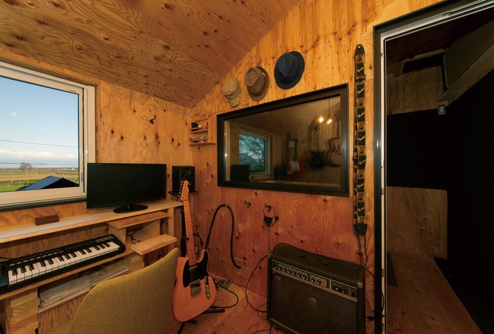 豊かな自然が望めるレコーディングスタジオ。アンプやギター、エフェクターなどの必要機材がずらり