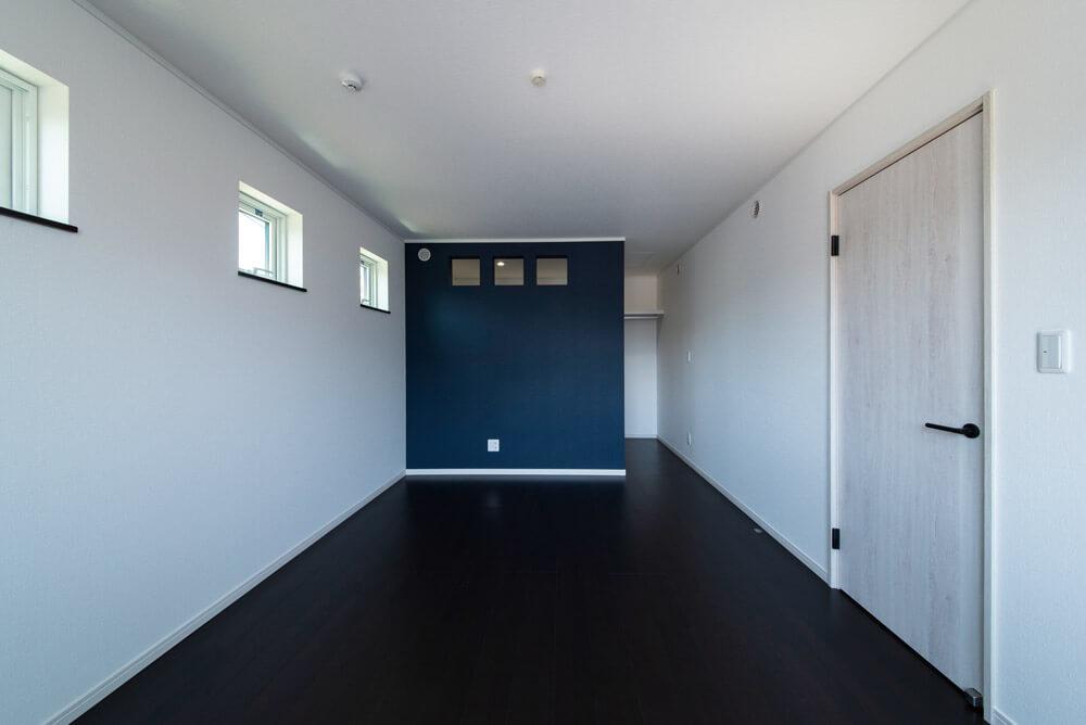 寝室は高い位置に小さめの窓を設けて落ち着いて休める空間に。ネイビーのアクセントウォールが効果的