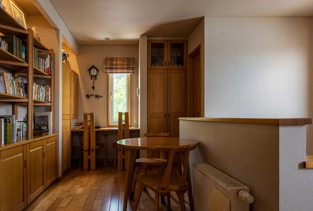 3階階段ホールにも蔵書をたっぷりしまえる本棚とカウンターを造作し、書斎コーナーに。家具も無垢材で揃え、統一感をもたせて。正面の造作収納の上は、現場着工の際、安全祈願を行う神棚がまつられている