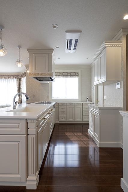 白を基調にしたキッチンは、造作仕様で収納もたっぷり。さらに冷凍・冷蔵庫置き場やパントリーも、キッチンに隣接して設けられている