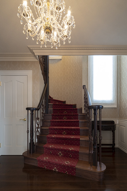 玄関ホールから美しいアールを描いて2階へ続く階段。天井のシャープなモールや手すりの滑らかなカーブもまた、匠の技によるもの
